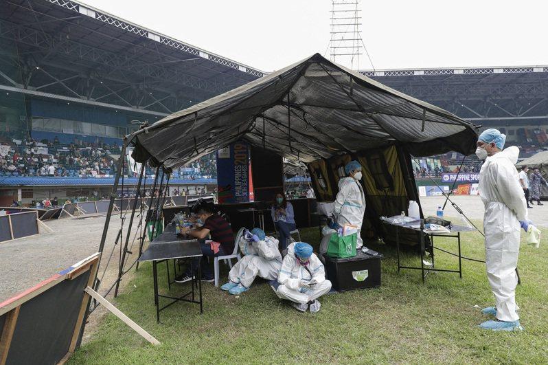 菲國確診數連兩天創新高,圖為7月28日馬尼拉一處體育館內,臨時檢測站醫護人員穿著防護衣休息的畫面。美聯社