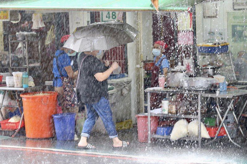 輕度颱風哈格比今天影響台灣最劇烈,中央氣象局今天針對全台11縣市發布大雨特報。台北不時有間歇式性大風大雨,民眾在大雨間移動。記者林伯東/攝影