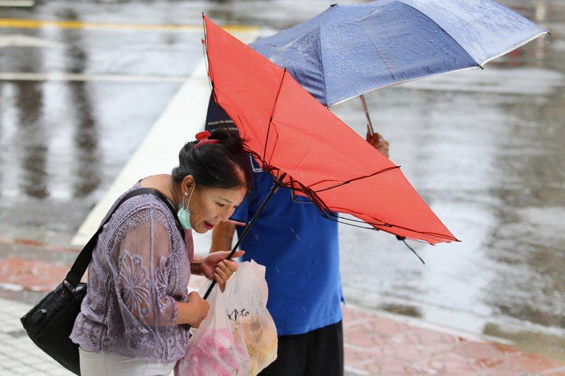 颱風哈格比今天影響台灣最劇烈,台北不時有間歇性大風大雨,民眾在大雨間移動。圖/林伯東