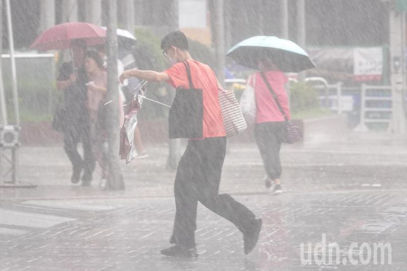 輕度颱風哈格比今天影響台灣最劇烈,中央氣象局今天針對全台11縣市發布大雨特報。台北車站前的行人被強風和大雨襲擊的相當狼狽。記者季相儒/攝影