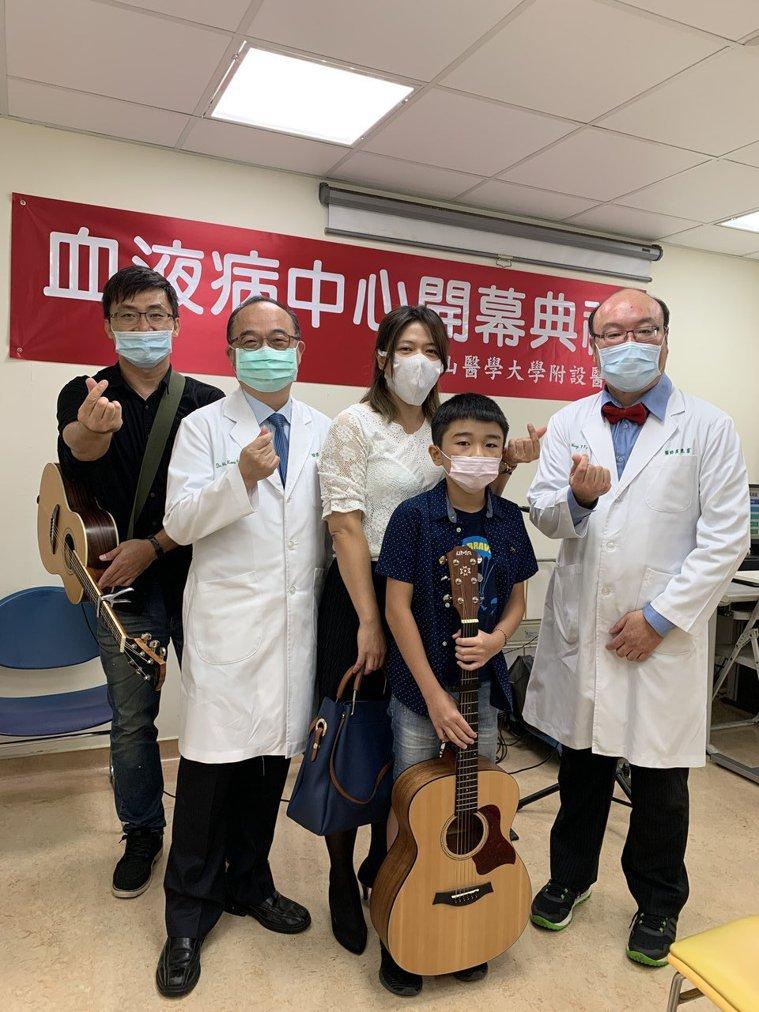 台中市中山醫學大學附設醫院上午成立「血液病中心」,患者李小弟(中)現場演奏吉他祝...