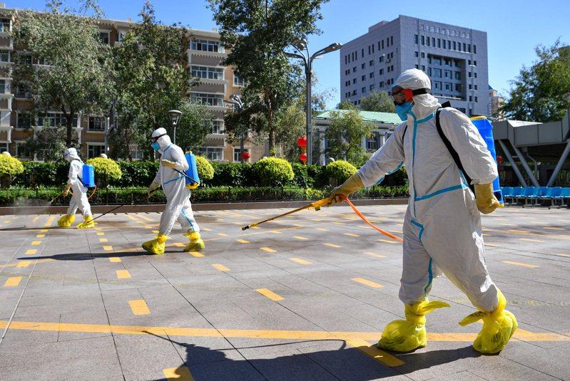 圖為位於烏魯木齊的新疆維吾爾自治區人民醫院,工作人員正在對核酸檢測等候區域進行消毒。新華社