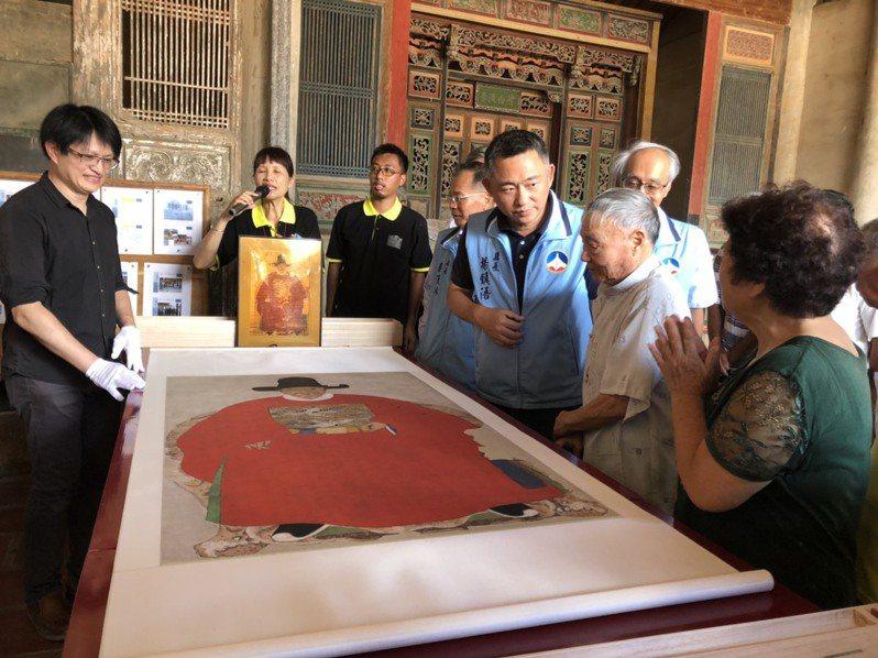 畫像修復師范定甫(左)展示修復的蔡復一畫像複製品,金門縣長楊鎮浯與鄉親讚嘆。記者蔡家蓁/攝影