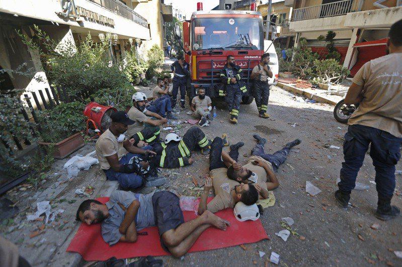 疲憊的救援人員在黎巴嫩首都貝魯特街頭休息。 新華社