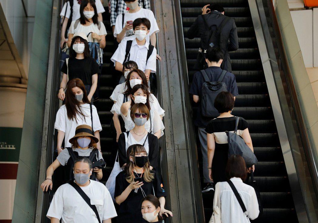 日本新冠肺炎疫情持續升溫。圖為日本東京的民眾於外出時配戴口罩防疫。 路透社