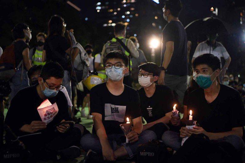 圖為今年6月4日黃之鋒(中)等人在維園參與未經警方批准的「六四」燭光晚會。 圖/中通社