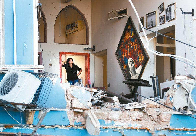 黎巴嫩首都貝魯特四日發生大爆炸,一名婦人五日站在滿目瘡痍的餐廳內,一臉無奈。(美聯社)