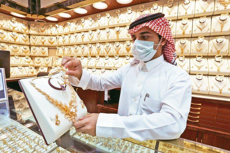 金價續創新高,沙烏地阿拉伯一名珠寶商向顧客展示金項鍊。 (路透)
