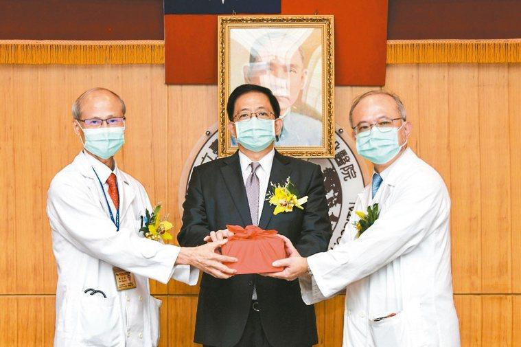 台大醫院新舊任院長吳明賢(右)、陳石池(左)交接,由台大校長管中閔監交。圖/台大...