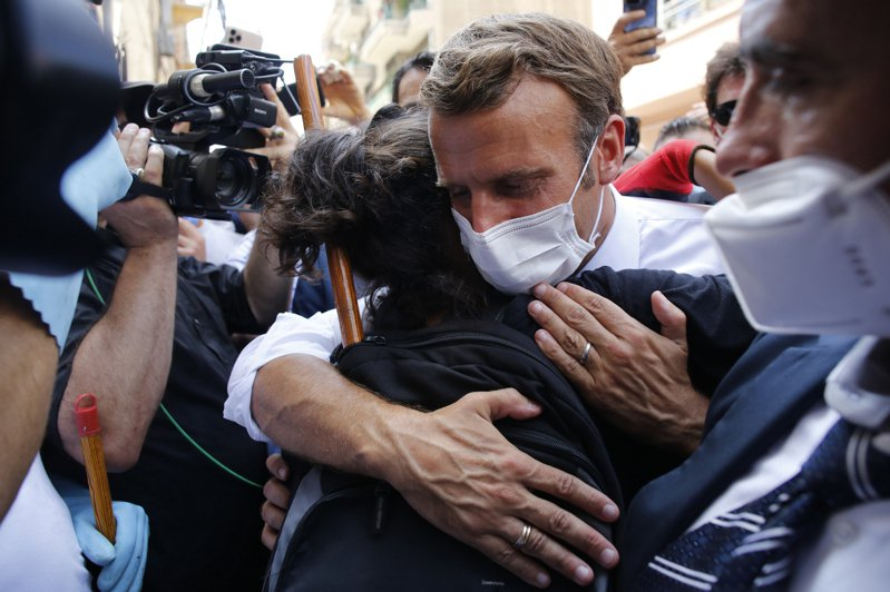 前往貝魯特探視災情的法國總統馬克宏六日與當地居民擁抱。(美聯社)