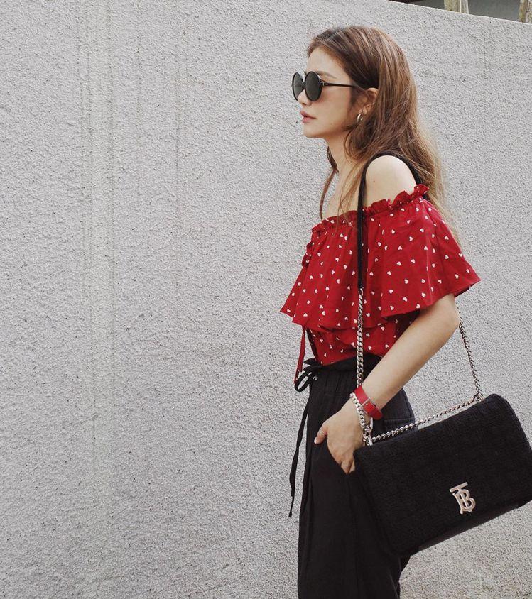 身穿紅色波點平肩上衣、黑色寬褲,許路兒以黑色款中型絎縫毛巾布Lola包配襯。圖/...