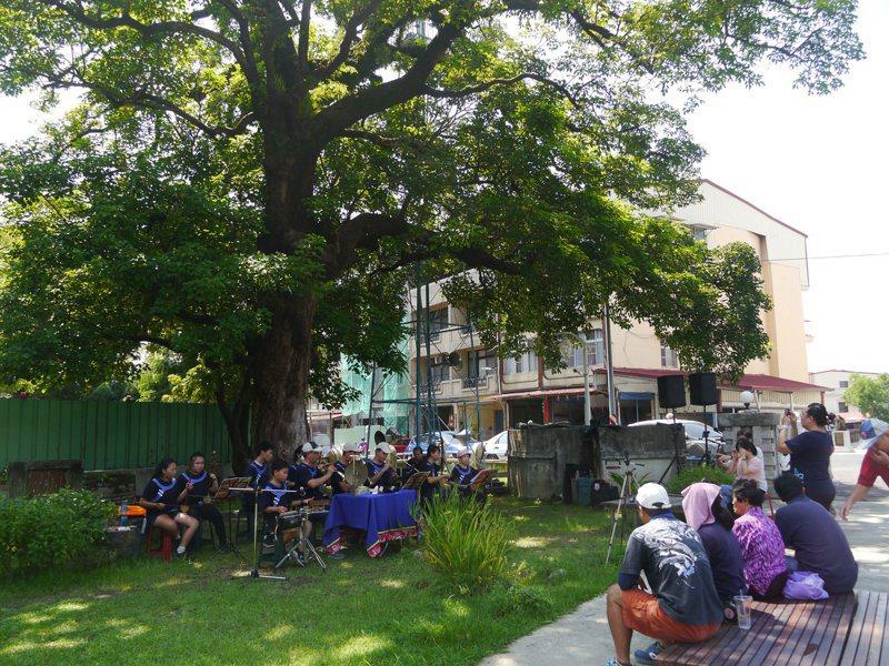 高雄市美濃搖籃咖啡利用假日推出「閱讀搖籃市集」,居民在老樹下聆聽客家八音演奏。記者徐白櫻/攝影