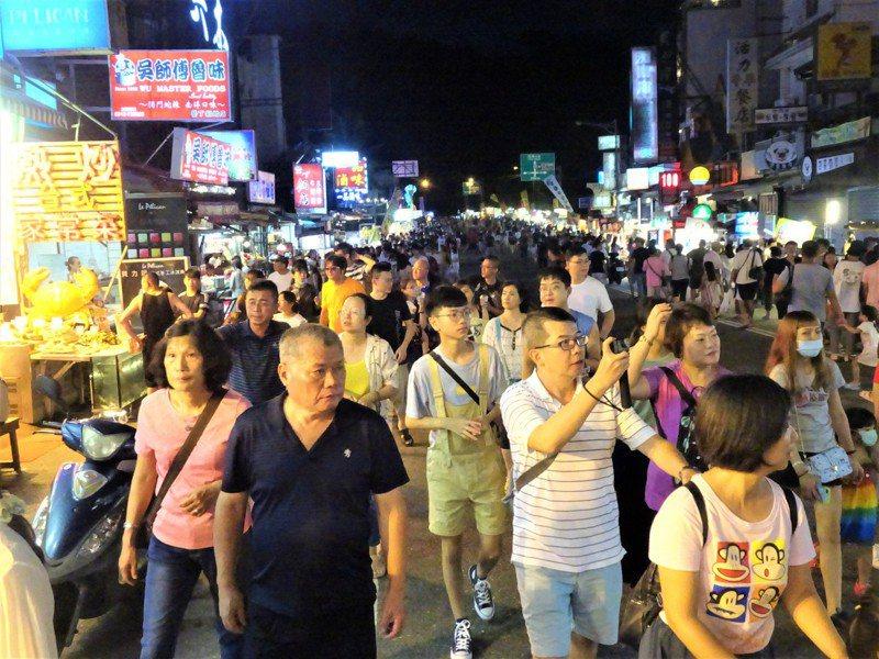 墾丁大街今天入夜後人潮湧現,警方晚上6時起在大街兩側入口實施人車分流,估計約三成的遊客戴口罩,攤商也不到一半。記者潘欣中/攝影