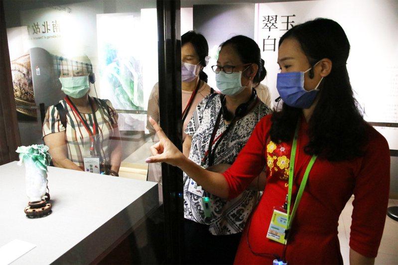 越南新住民范氏月(右1)指出翠玉白菜只有18公分高,但卻雕工精細,令人陶醉。記者廖炳棋/翻攝
