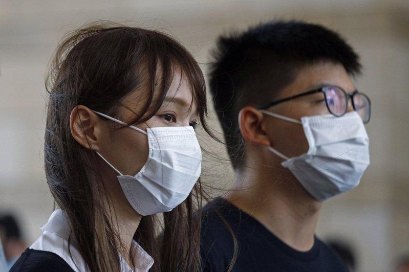 前「香港眾志」核心成員周庭(左),10日晚間遭香港警方以涉嫌違反港版國安法為由逮捕。右為另一成員黃之鋒。 美聯社