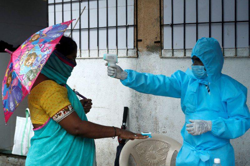 路透社統計顯示,全球新冠肺炎染疫人數10日突破2000萬大關。圖為印度孟買的新冠肺炎檢查營,醫護人員量測居民的體溫。 路透社