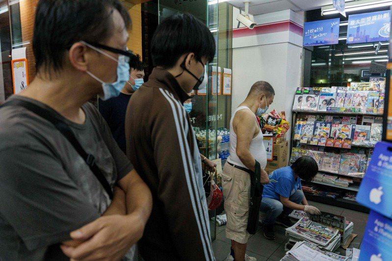 11日天未亮,許多香港民眾已經上街搶買蘋果日報。法新社