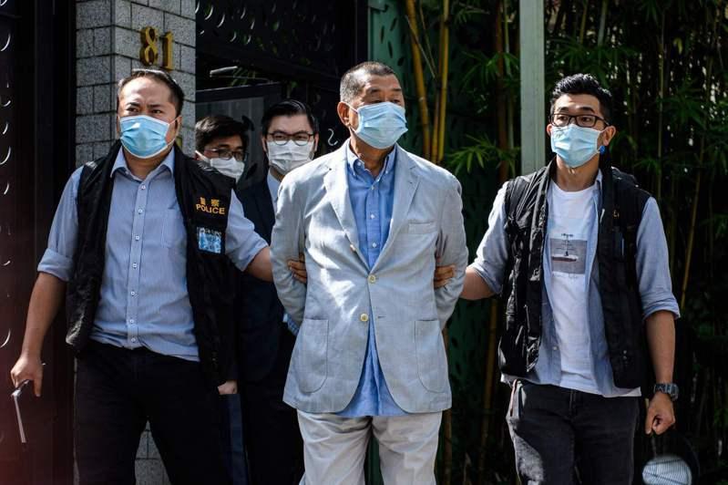 香港警方10日以涉嫌違反港區國安法為由,大舉抓捕香港壹傳媒創辦人黎智英(前中)等十人。圖為黎智英被上手銬,帶離家中。 美聯社