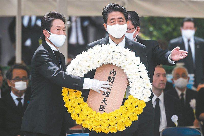 日本首相安倍晉三(中)九日在長崎市原爆七十五周年紀念儀式獻上花圈。(法新社)