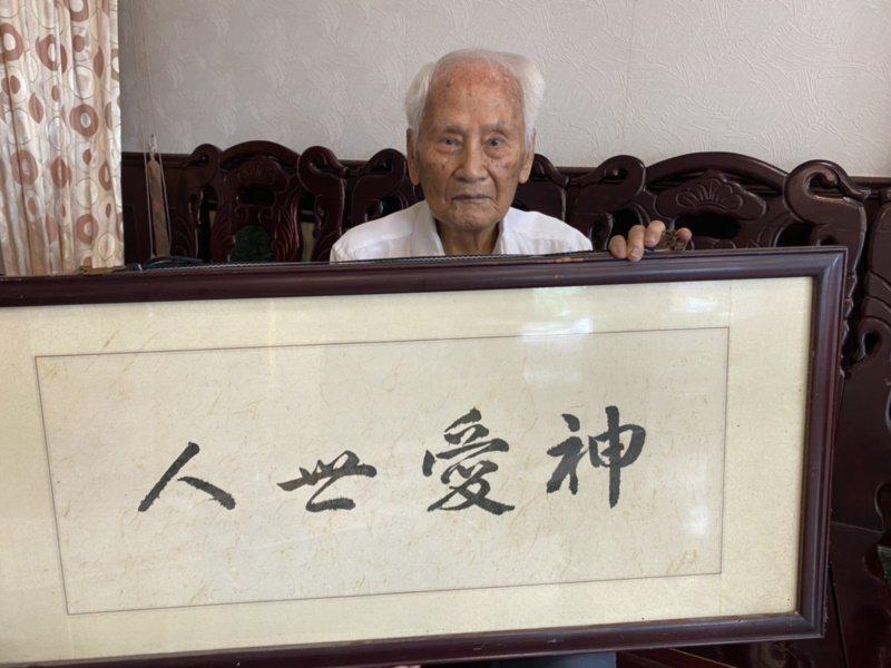 信奉基督教的理髮老師傅沈駿魁(右)寫了一手好書法,這幅「神愛世人」就是出自他的手...