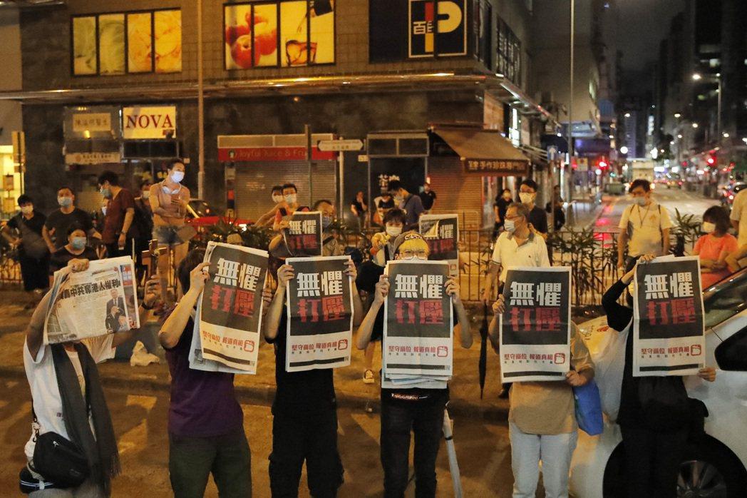 黎智英深夜獲准保釋離開警署時,數名支持者手持蘋果日報印有「無懼打壓」幾個大字的報...