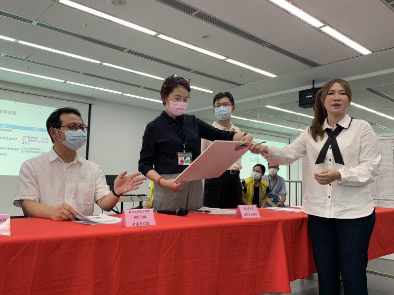 台北市議員陳怡君(右)昨天拿著「不漏水保證書」到場,副市長黃珊珊(左2)僅收下手板,口頭表示市府責無旁貸。記者趙宥寧/攝影