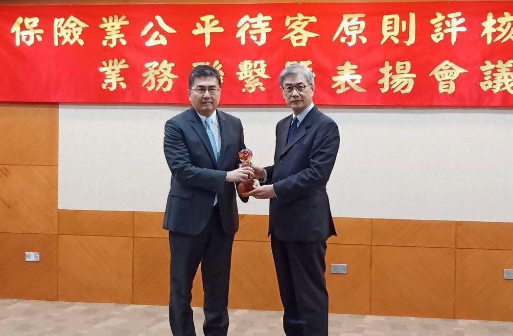 新安東京海上產險總經理林榮泰(左)代表出席接受金管會主委黃天牧(右)頒獎。新安東...