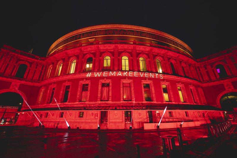 英國皇家阿爾伯特音樂廳亮起紅燈和「#我們辦活動」標語,為受疫情影響的演藝活動業者聲援。圖/RoyalAlbertHall推特