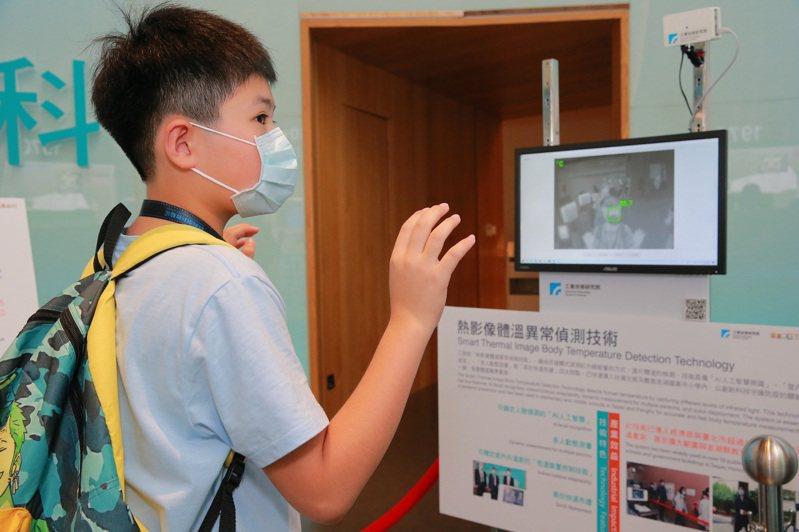 參訪學員操作熱影像體溫異常偵測技術,對精準高效率的系統大感新鮮。圖/工研院提供