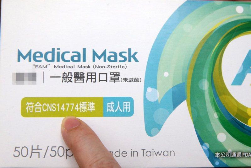 審視外盒是否印有CNS14774字號及醫用口罩等字樣。記者胡經周/攝影
