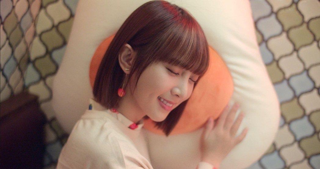 溫妮親密擁抱溫泉蛋(粉絲暱稱)抱枕,象徵自己對歌迷滿滿的愛。圖/哈囉你好工作室提...