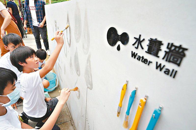 小朋友在戶外水畫牆畫出水滴圖案。圖/新竹市政府提供
