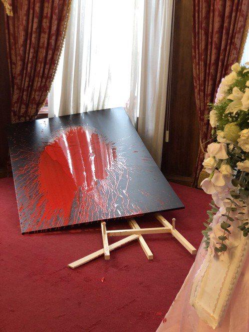 李登輝追思會場遭到一名女子鬧場,她以預藏裝有紅色油漆的氣球,砸向會場內祈禱室擺放的李登輝肖像。 圖/讀者提供