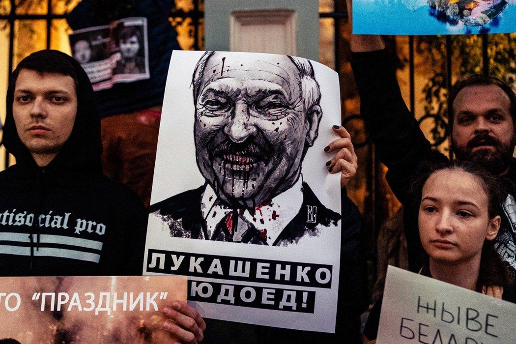 圖為駐莫斯科的白俄羅斯使館前,抗議群眾舉著盧卡申科的諷刺畫像。 圖/法新設