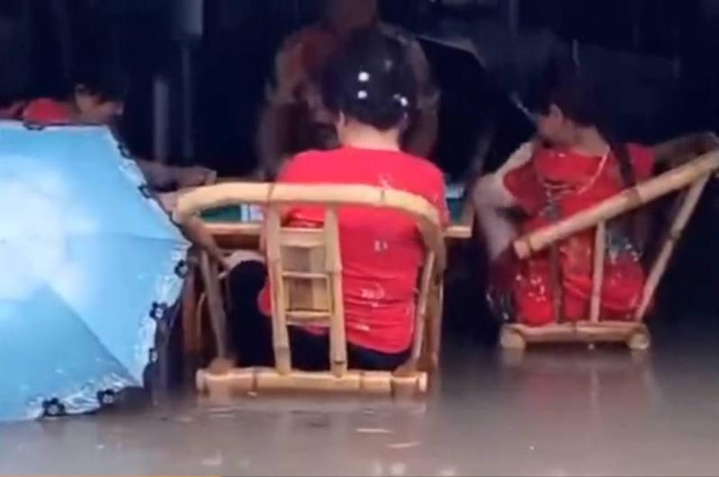 成都大媽被洪水圍困,仍面不改色打麻雀。(影片截圖)