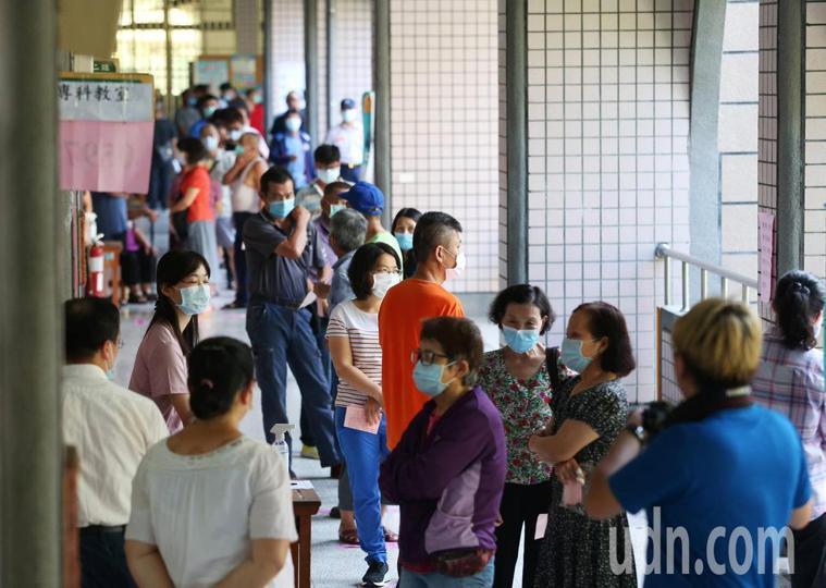 高雄市長補選投票今天登場,疫情警報未解除,規定投票民眾必須戴口罩,進投票所配合量...