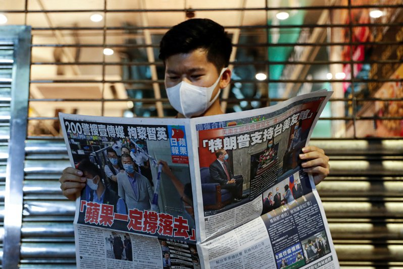 一位香港民眾11日購買香港蘋果日報,支持該報創辦人黎智英。路透