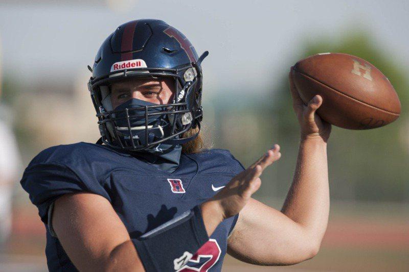 美國猶他州高中美式足球隊員練習時,雖隔著頭盔,還是戴了口罩。法新社