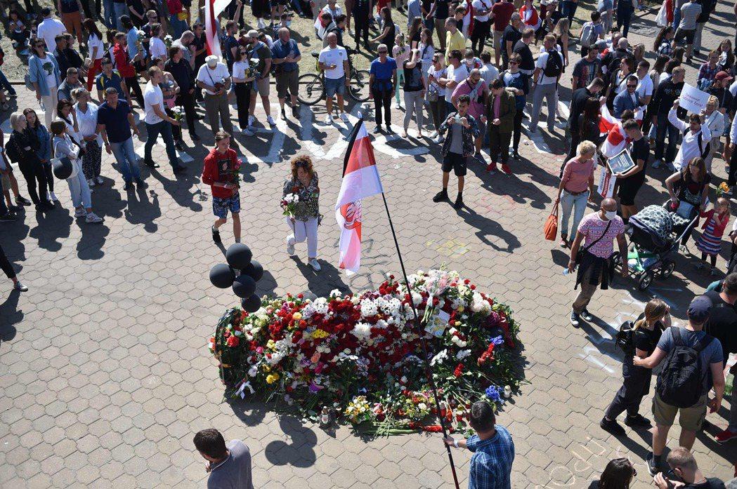 白俄羅斯民眾15日聚集在明斯克市區,為10日死亡的男子獻花悼念。(法新社)