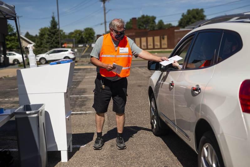 擔心郵政遲緩,明尼蘇達州選民在家將選票投好,11日帶到指定「得來速」地交給站在指定地點的法官收集,由法官收集,保證選票不會因為日期失效而作廢。 法新社