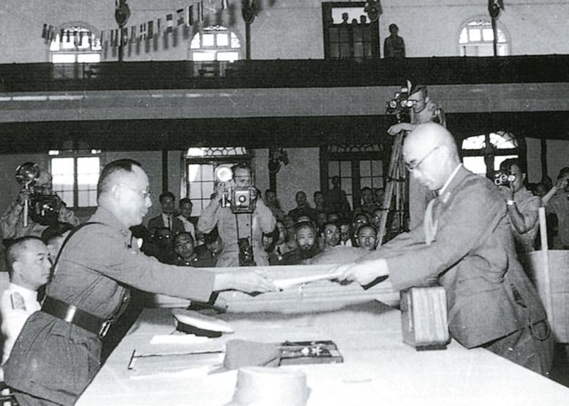 1945年9月9日的南京受降典禮,日本駐華派遣軍總司令岡村寧次簽署降書後,由參謀長小林淺三郎(右)呈遞給何應欽(左)。 圖/國防部提供