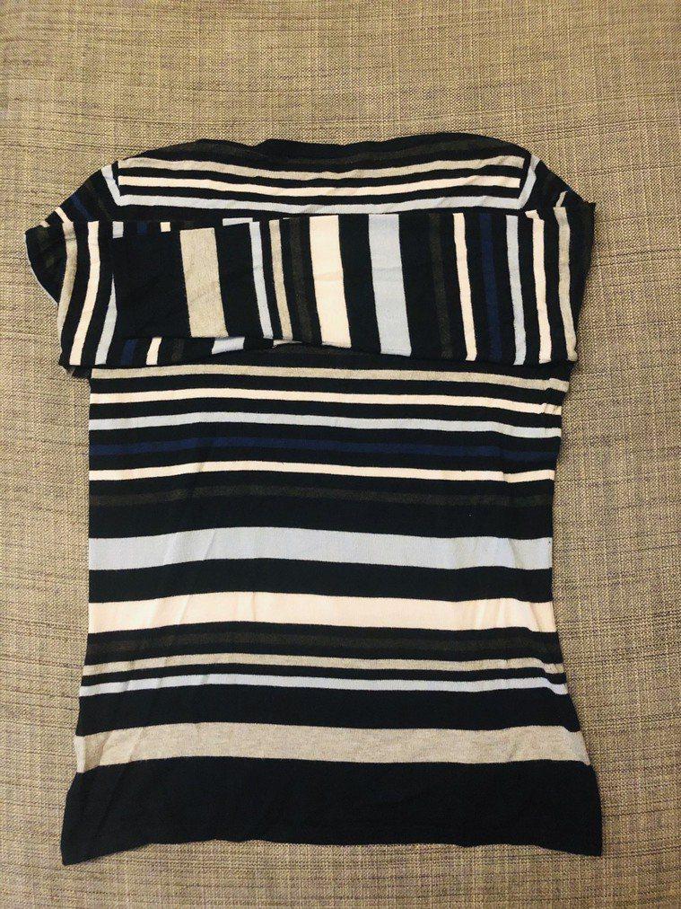 1.將上衣正面朝下,兩邊袖子平摺與領口對齊。