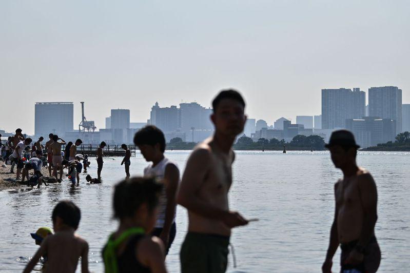 日本近日飽受夏季熱浪之苦,圖為民眾在東京灣台場沙灘戲水。法新社