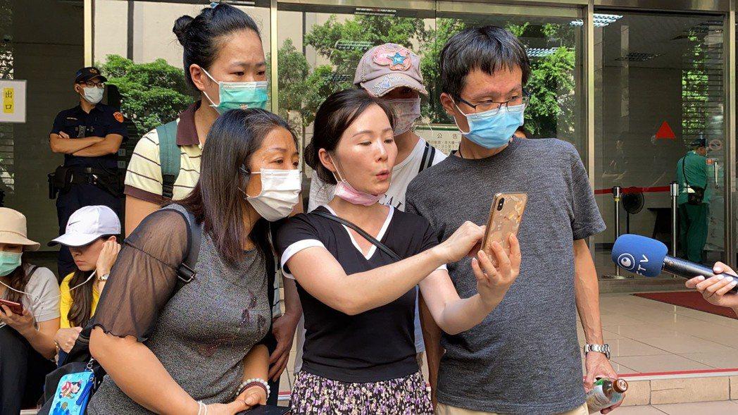 一群小明父母今日下午前往疾管署陳情,聽聞小明返台政策鬆綁,看著手機上顯示的新聞確...