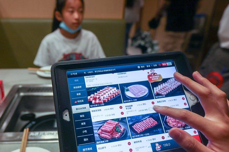 8月15日,上海市一名消費者點餐時選擇半份菜。 圖/新華社