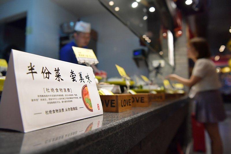 中國至少18個省份的餐飲烹飪行業協會,要求當地餐飲業限制顧客點餐。圖為南昌市飯店推出半份菜點菜模式。 圖/新華社