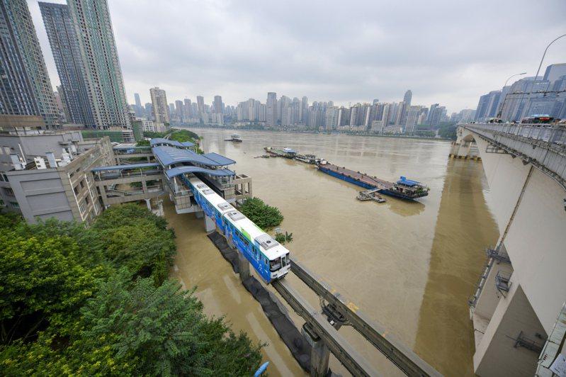 長江、嘉陵江洪峰19日抵達重慶市主城區,輕軌行駛在嘉陵江濱江路,下面的路面已被洪水淹沒。 圖/新華社