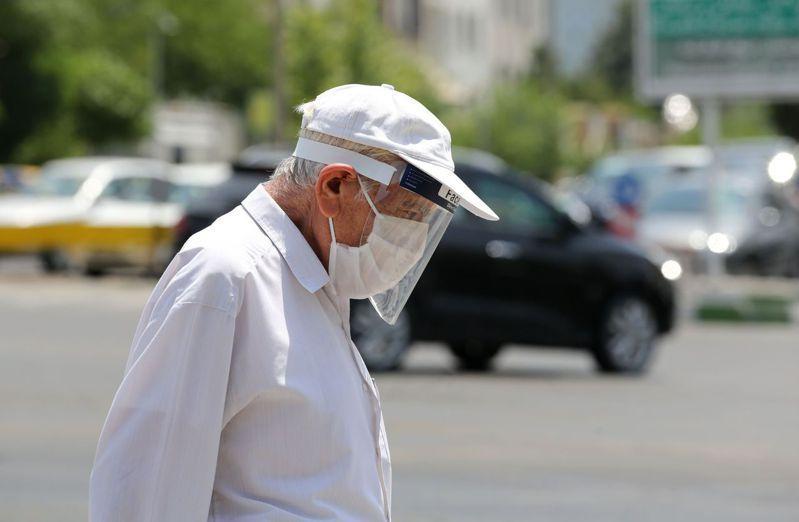 伊朗全國各地爆發第3波新型冠狀病毒疫情,圖為德黑蘭街頭上一位戴著口罩與防護面罩的民眾。 法新社資料照