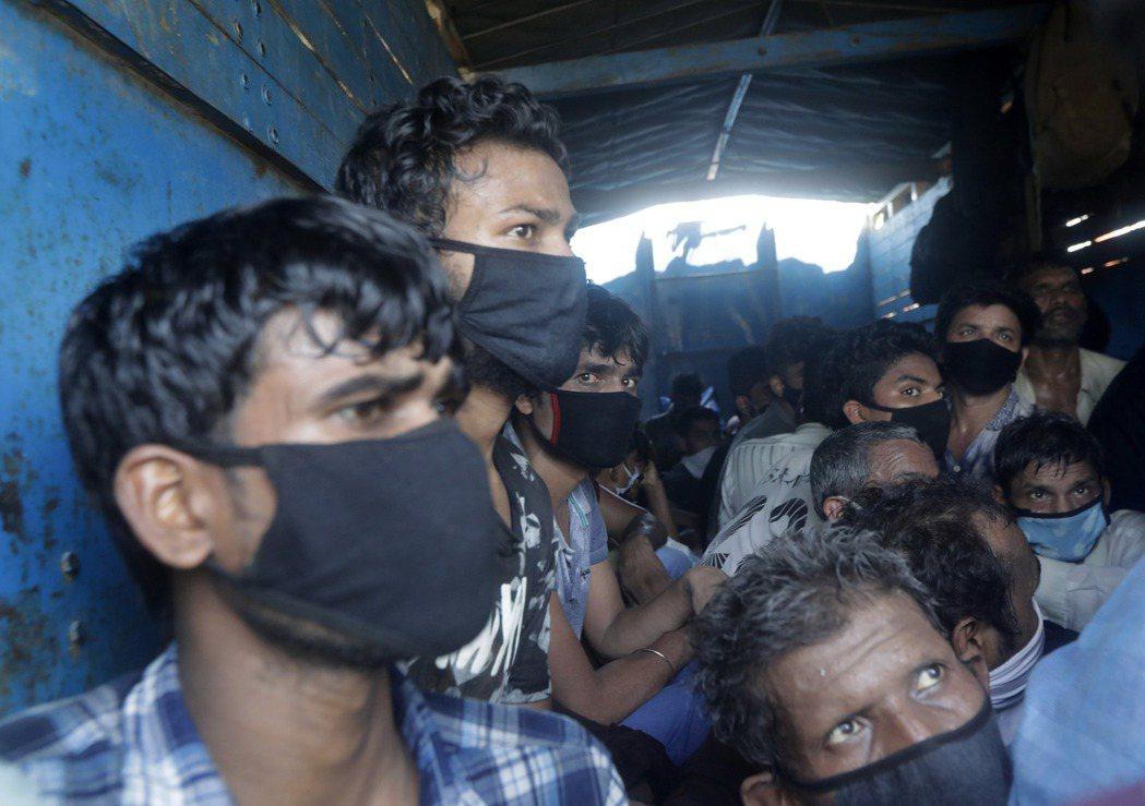 圖為印度來自北方邦的城市移工5月時搭乘卡車返鄉。美聯社