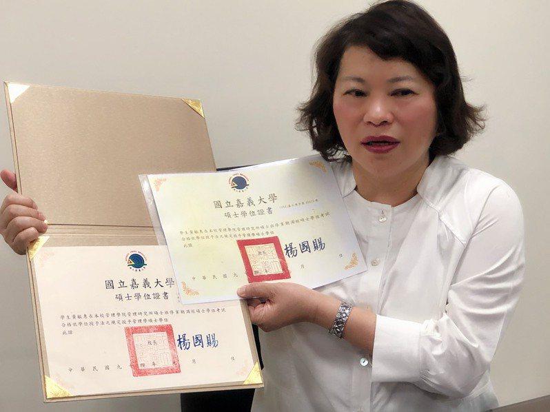 嘉義市長黃敏惠昨天出示嘉義大學碩士學位證書,表示「真金不怕火煉」。 記者李承穎/攝影